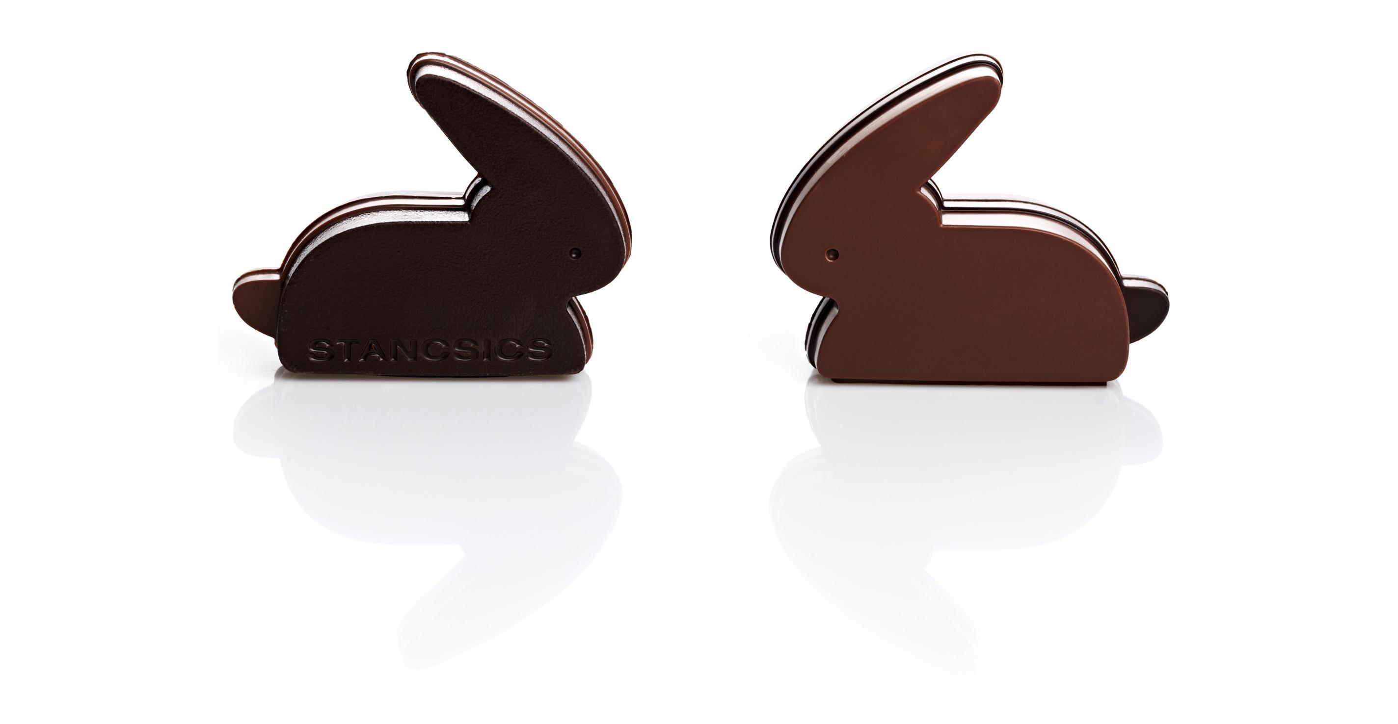 zwei moderne, dynamische schokohasen stehen sich schnäutzchen zu schnäutzchen gegenüber in vollmilchschokolade und in edelbitterschokolade