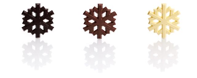 drei edle eiskristalle aus verschiedenen schokoladensorten auf weißem hintergrund