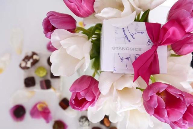 ST. Pralinen und Trüffel unter einem frühlingsstrauss . im tulpenstrauß eine pralinenschachtel mit pinkfarbener schleife