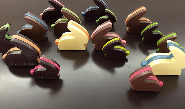 hasen aus weißer, vollmilch und dunkler schokolade auf dunklem hintergrund, ostern, bunte hasen beim hasentreffen
